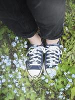 jambes en baskets bleues sur l'herbe photo