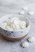 petites meringues blanches dans le bol en céramique photo
