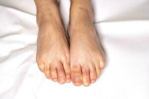 femme pied flexion sur les draps couleur blanc photo