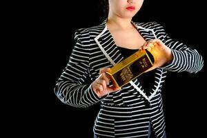 femme d'affaires tenant le lingot d'or sur fond noir photo