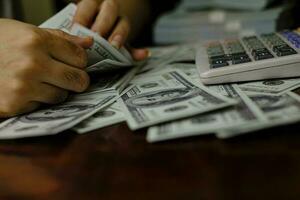 hommes d'affaires femmes comptant de l'argent sur une pile de billets de 100 dollars américains photo