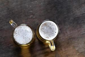 vue de dessus de la bière en verre sur le fond de la table en bois photo