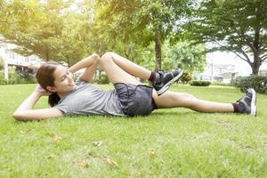 belle femme sportive fait des exercices dans un parc verdoyant photo