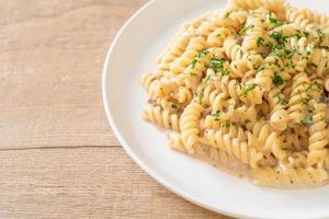 spirali ou sauce à la crème de champignons de pâtes en spirale avec du persil - style de cuisine italienne photo