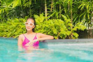 Portrait belle jeune femme asiatique se détendre sourire autour de la piscine extérieure de l'hôtel resort photo