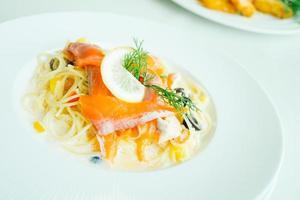 pâtes ou sauce à la crème de spaghetti avec de la viande de saumon et du citron sur le dessus photo
