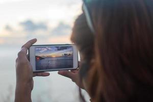 personne prenant une vidéo du coucher du soleil avec un téléphone intelligent photo