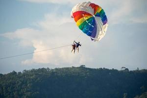 parachute ascensionnel au-dessus de la mer avec un beau fond de ciel bleu à la plage de patong, phuket, thaïlande. socus doux. photo