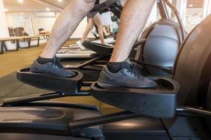 homme utilisant une machine elliptique dans la salle de sport photo