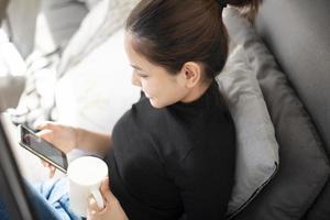 belle jeune femme se reposant sur un canapé à la maison et utilisant un téléphone intelligent photo