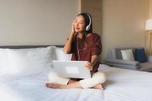portrait de belles jeunes femmes asiatiques utilisant un ordinateur et un casque pour écouter de la musique photo