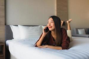Portrait de belles jeunes femmes asiatiques utilisant un téléphone portable sur le lit photo