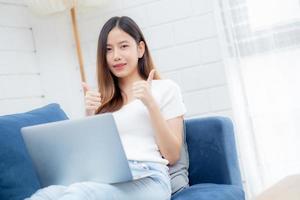 jeune femme d'affaires asiatique sourit et travaille à domicile avec un ordinateur portable en ligne sur Internet sur un canapé dans le salon, une fille indépendante utilisant un ordinateur portable sur un canapé avec confort, nouveau concept de mode de vie normal. photo