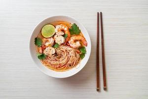 nouilles avec soupe épicée et crevettes dans un bol blanc, ou tom yum kung - style cuisine asiatique photo