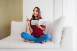Portrait de belles jeunes femmes asiatiques lire un livre sur une chaise de canapé photo