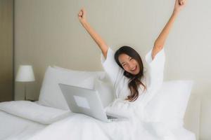 Portrait de belles jeunes femmes asiatiques avec une tasse de café et un ordinateur portable sur le lit photo