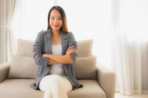 Portrait de belles jeunes femmes asiatiques sourire heureux se détendre assis sur une chaise canapé photo