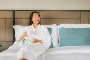 Portrait de belles jeunes femmes asiatiques avec une tasse de café sur le lit photo