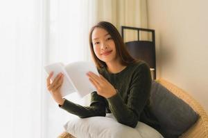 Portrait de belles jeunes femmes asiatiques lisant un livre et assis sur une chaise de canapé photo