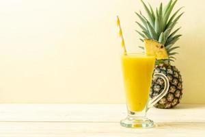 verre de smoothie ananas frais sur table en bois - boisson saine photo