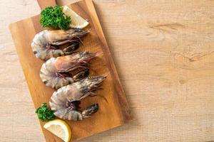 crevettes tigrées fraîches ou crevettes sur planche de bois photo