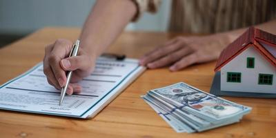 gros plan de l'agent immobilier avec la main du modèle de maison mettant la signature du contrat, la signature d'accords modestes au bureau. concept immobilier, déménagement ou location de propriété photo