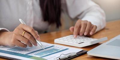 femme avec rapport financier et calculatrice. femme à l'aide de la calculatrice pour calculer le rapport à la table au bureau photo