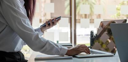 Image en gros plan d'une femme tenant et utilisant un téléphone portable et utilisant un ordinateur photo