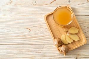 verre de jus de gingembre frais et chaud aux racines de gingembre - style de boisson saine photo
