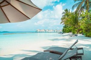 chaises de plage avec l'île tropicale de l'hôtel de villégiature maldives et le fond de la mer photo