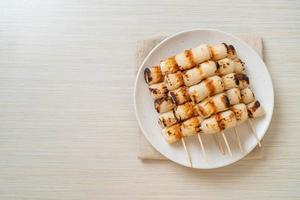 Gâteau de pâte de poisson en forme de tube grillé ou brochette de calmar en tube sur plaque photo