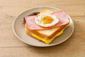 pain fait maison fromage grillé garni de jambon et oeuf au plat avec saucisse de porc pour le petit déjeuner photo