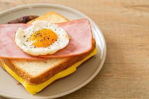 pain maison, fromage grillé, jambon garni et œuf au plat avec saucisse de porc pour le petit-déjeuner photo