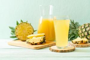 jus d'ananas frais sur fond de bois photo