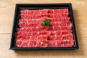 boeuf frais cru tranché avec texture marbrée servi pour sukiyaki et shabu ou yakiniku photo