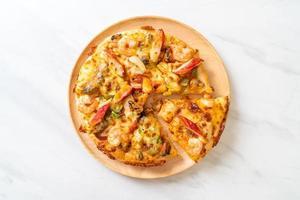 fruits de mer de crevettes, poulpes, moules et pizza au crabe sur plateau en bois photo