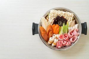 budae jjigae ou budaejjiga, ragoût de l'armée ou ragoût de la base de l'armée. il regorge de kimchi, de spam, de saucisses, de nouilles ramen et bien plus encore - le style populaire de la fondue coréenne photo