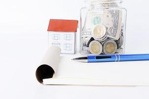 stylo bleu avec bloc-notes et maison en papier et bouteilles en verre photo