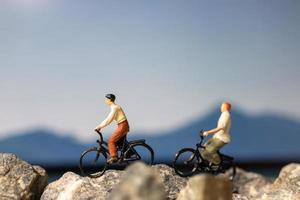 voyageur miniature avec vélo sur le rocher photo
