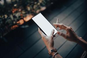 les mains et le smartphone de la femme avec des cigarettes. photo