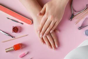 procédure de soin des ongles dans un salon de beauté. mains féminines et outils de manucure sur fond rose. concept spa soins du corps. photo