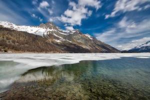 paysage de montagne dans la vallée de l'engadine avec un jeu de lumières au dégel du lac photo