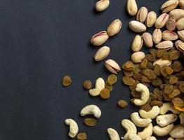 mélange sain de fruits secs et de noix sur fond sombre. amandes, pistache, noix de cajou, raisins secs photo