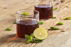 tasse de thé au gingembre, citron et menthe sur table en bois photo