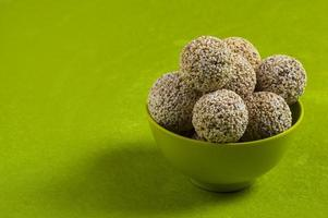 amarante ou rajgira laddu, cholai ke laddo dans un bol vert sur fond vert photo