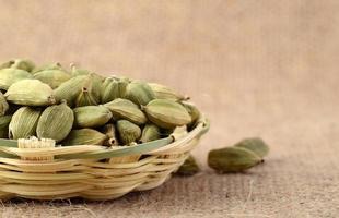 Gousses de cardamome verte dans un panier en bambou sur un sac en tissu photo