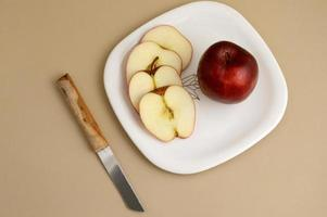 délicieuse pomme et tranche dans une assiette blanche avec couteau et fourchette photo