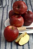 De délicieuses pommes dans une assiette avec un couteau sur une nappe à rayures photo