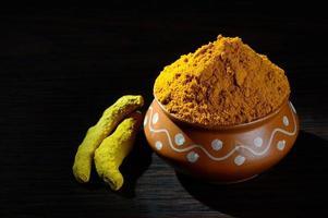 poudre de curcuma dans un pot en argile avec des racines ou des écorces sur fond noir photo