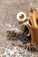 épices et herbes. ingrédients de la nourriture et de la cuisine. bâtons de cannelle, étoiles d'anis, grains de poivre noir sur fond texturé photo